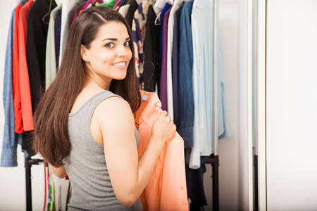 getting dressed: Gorgeous young Hispanic woman deciding what to wear and getting dressed in a dressing room at home Stock Photo
