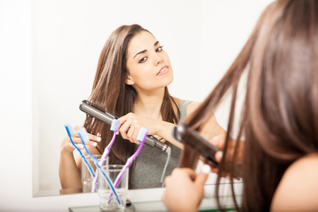 flat iron: Pretty young woman using a flat iron to straighten and style her hair in a bathroom Stock Photo