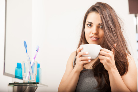 messy: Portrait of a pretty young brunette with messy hair drinking some coffee to wake up and get ready for work Stock Photo
