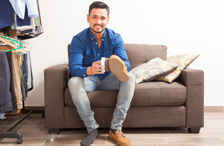 Portrait of a young Hispanic man with a beard polishing his shoes in a dressing room and getting ready for work