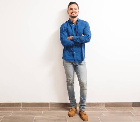 leaning: Full length portrait of a young and confident Hispanic man standing against a white wall with his arms crossed and smiling Stock Photo