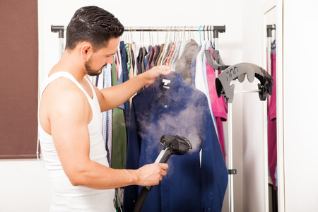 Profile view of a good looking young man using a steamer on a shirt before getting dressed Stockfoto