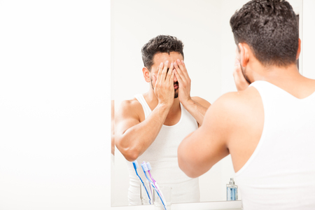 water splashing: Young man trying to wake up and splashing some water on his face in the morning in a bathroom Stock Photo
