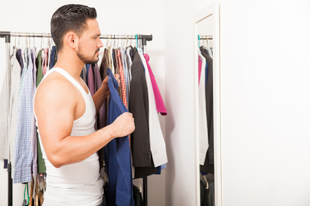 getting dressed: Profile view of a young man trying a shirt on in front of a mirror while getting dressed in his bedroom