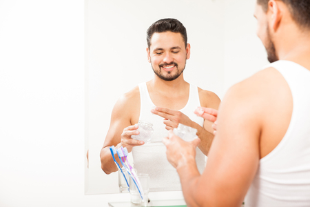 hair gel: Portrait of a happy young Hispanic man styling his hair with some gel in front of a mirror in the bathroom