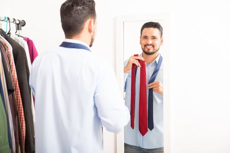 Portrait of a happy young man getting dressed and choosing a tie in front of a mirror and making eye contact Stock Photo