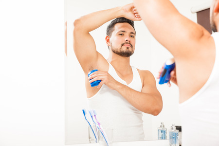 Good looking young man with a beard putting on some deodorant in front of a mirror in a bathroom