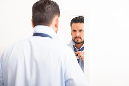 vistiendose: Retrato de un hombre joven y guapo atar un nudo en una corbata delante de un espejo en un vestidor