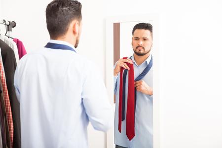 vistiendose: Retrato de un hombre joven y guapo que consigue vestido en un dormitorio y la elecci�n de la corbata adecuada para el trabajo Foto de archivo