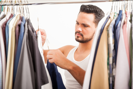 vistiendose: Individuo hermoso con una barba que se coloca delante de su armario y la comparación de un par de camisas de vestir Foto de archivo