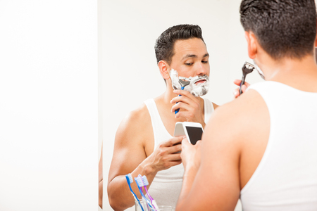 busy beard: Portrait of a busy and distracted young man multitasking and shaving his beard while texting on his smartphone