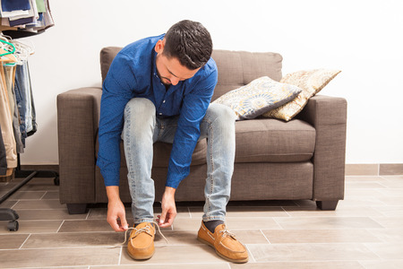 getting ready: Man dressed casually tying his shoes while sitting in a couch in a dressing room Stock Photo