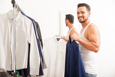 Portrait of a young Hispanic man deciding what to wear in a dressing room and smiling