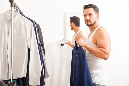 dressed: Attractive and strong young man choosing between to shirts to wear while getting dressed in a dressing room
