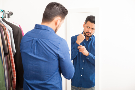 young  cuffs: Portrait of a handsome young Hispanic man getting dressed on casual clothes in front of a mirror