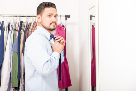 getting ready: Profile view of a handsome young Latin man getting ready for work and putting on a tie in a dressing room Stock Photo