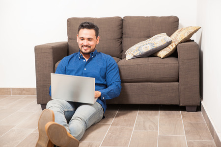telecommuting: Handsome young man sitting on the floor at home and using a laptop computer