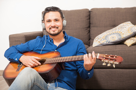 composer: Portrait of a good looking young musician and composer playing the guitar at home and smiling