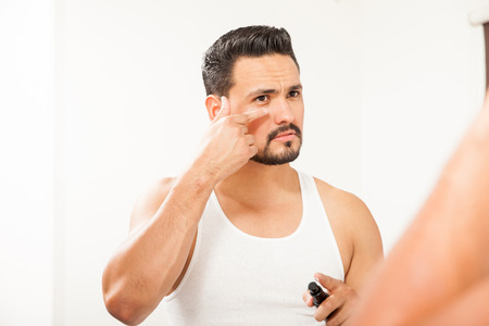 putting on: Good looking Hispanic young man putting on some anti-aging cream to prevent bags under eyes in the bathroom