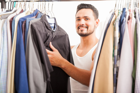 choosing: Handsome young Hispanic man looking at his closet and finding the right shirt for work and smiling