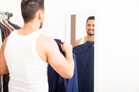 getting dressed: Good looking young man getting dressed and trying on a shirt in front of a mirror in a dressing room