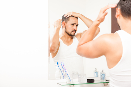 male hair: Portrait of an attractive young Hispanic man styling his hair in front of a mirror using some gel
