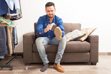 vistiendose: apuesto joven con una barba pulir sus zapatos y vestirse en casa
