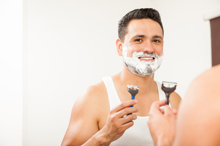 good looking guy: Portrait of a good looking guy shaving off his beard with a razor in the bathroom and smiling