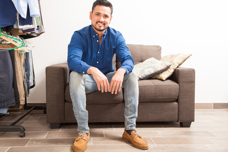 getting dressed: Portrait of an attractive young man with a beard just finished getting dressed and sitting on a couch at home Stock Photo