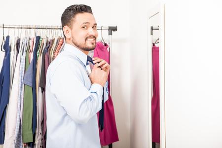 vistiendose: Retrato de un hombre joven hermoso que pone en una corbata y vestirse en un vestidor en casa Foto de archivo