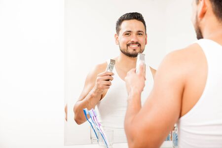 electric trimmer: Portrait of a good looking Hispanic young man holding an electric razor and shaving his beard in the bathroom Stock Photo