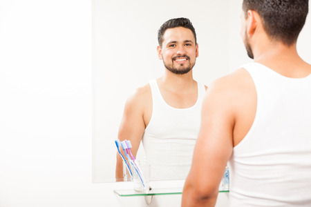 eye contact: Portrait of a happy young attractive man with a beard standing in front of a bathroom mirror and making eye contact Stock Photo