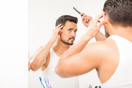 Portrait of a handsome young man with a beard using a comb to style his hair in front of a bathroom mirror