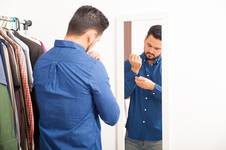 young  cuffs: Attractive guy with a beard getting dressed and buttoning his shirt in front of a mirror