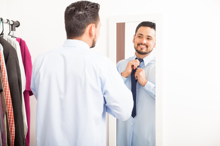getting dressed: Handsome young man getting dressed and putting on a necktie in front of a mirror in a dressing room at home