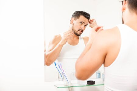 hair man: Handsome guy getting ready for work and combing his hair in front of a mirror in a bathroom