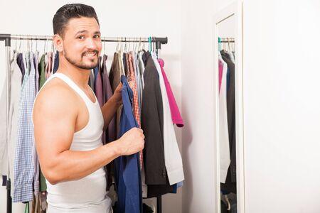 vistiendose: El individuo atractivo con una barba tratando una camisa delante de un espejo y vestirse