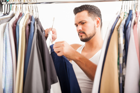 hombres guapos: Good looking young man choosing between to shirts to wear while looking through his closet Foto de archivo