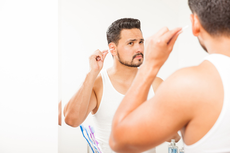 cotton swab: Portrait of an attractive young man with a beard using a cotton swab to clean his ears Stock Photo