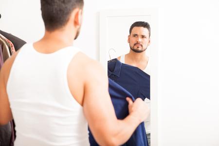 vistiendose: Retrato de un hombre joven con una barba de vestirse y tratar una camisa. Un mont�n de espacio de la copia