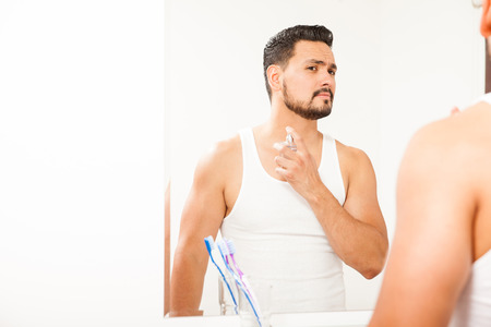 guys: Attractive young Hispanic man with a beard spraying some cologne on his neck