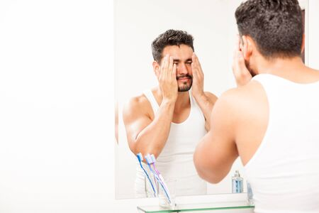 visage homme: Attractive young sleepy guy washing his face in the morning in front of a mirror in a bathroom Banque d'images
