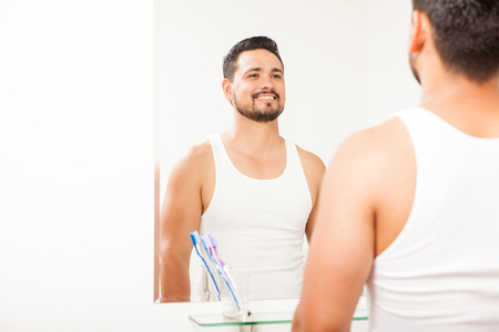 Attractive Hispanic young man looking at himself in a bathroom mirror in the morning and smiling