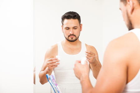 Good looking young man using dental floss in front of a mirror in the bathroom