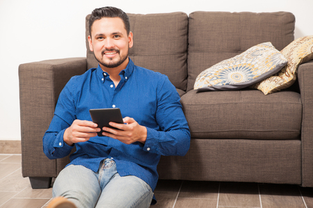 check out: Handsome young Hispanic man relaxing at home and using an e-reader to check out his favorite book Stock Photo