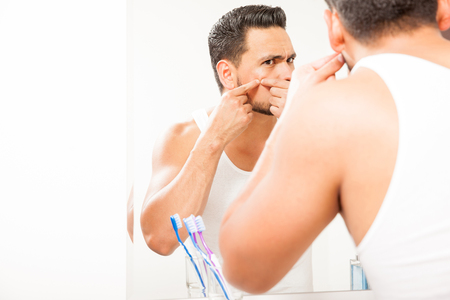 Good looking young man standing close to a mirror in the bathroom and squeezing a pimple on his face Stock Photo