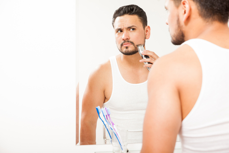 electric razor: Handsome young man using an electric razor to trim his beard in front of a bathroom mirror Stock Photo