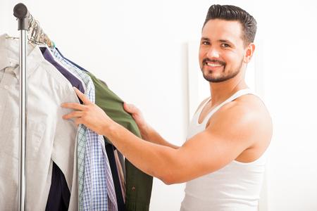 vistiendose: Retrato de un joven hispano feliz elegir qu� ponerse y vestirse en su habitaci�n