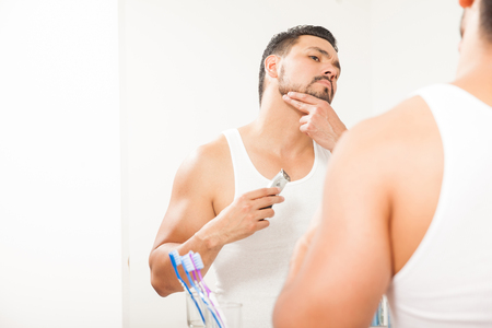 electric razor: Portrait of an attractive Latin young man using an electric razor to style his beard in front of a bathroom mirror