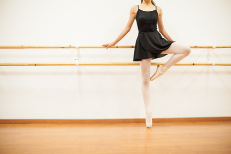 barre: Closeup of a beautiful young female dancer holding from a barre and standing on her toes in a dance academy
